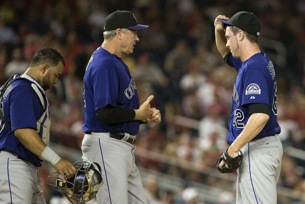 . Colorado Rockies relief pitcher Rob Scahill, right, is visited by catcher Wilin Rosario, left, and pitching coach Jim Wright during the fifth inning of a baseball game against the Washington Nationals at Nationals Park, on Monday, June 30, 2014, in Washington. (AP Photo/Evan Vucci)