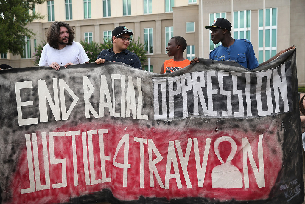 . SANFORD, FL - JULY 13: Demonstrators protest in front of the Seminole County Criminal Justice Center where a jury is deliberating in the trial of George Zimmerman on July 13, 2013 in Sanford, Florida. Zimmerman, a neighborhood watch volunteer, is on trial for the February 2012 shooting death of 17-year-old Trayvon Martin. (Photo by Scott Olson/Getty Images)