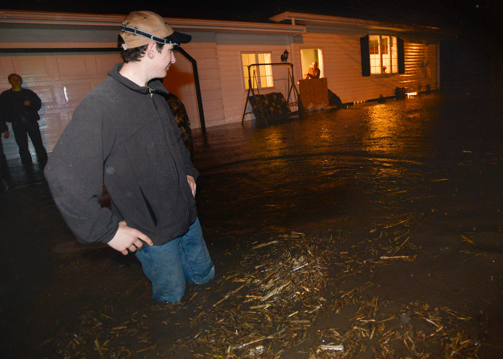. Jake Hodel, 15,  of Roanoke, Ill., stands in knee-high flood waters surrounding the home of Ross and Nancy Gingrich of Roanoke early Thursday, April 18, 2013, after heavy rains left many homes flooded out. The National Weather Service expected a storm system moving over Illinois would dump about three inches of rain in the area. (AP Photo/Journal Star, Ron Johnson)