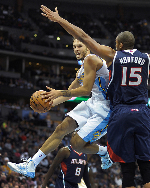 . Nuggets guard Evan Fournier looked for a way past Atlanta center Al Horford in the first half.   Photo By Karl Gehring/The Denver Post