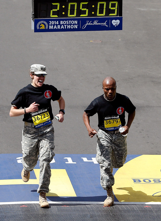 . Two soldiers cross the finish line of the 118th Boston Marathon on April 21, 2014 in Boston, Massachusetts.  (Photo by Jim Rogash/Getty Images)