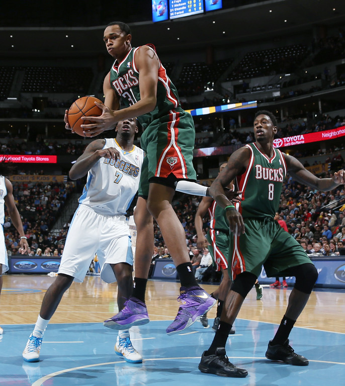 . Milwaukee Bucks forward John Henson pulls down a rebound in front of Denver Nuggets center J.J. Hickson, back left, as Bucks center Larry Sanders watches during the third quarter of the Nuggets\' 110-100 victory in an NBA basketball game in Denver on Wednesday, Feb. 5, 2014. (AP Photo/David Zalubowski)