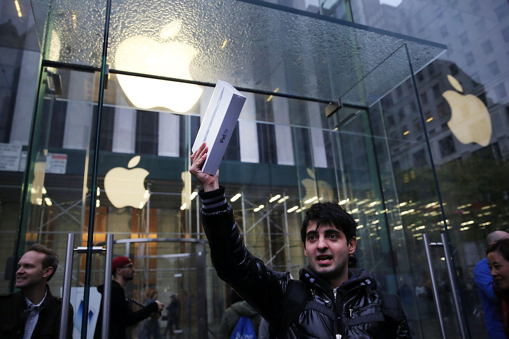 . The first customer in line, Rami Shamis, holds up his new iPad Air at the Apple Store on November 1, 2013 in New York City.  (Photo by Spencer Platt/Getty Images)