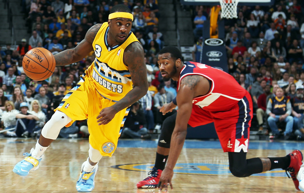 . Denver Nuggets guard Ty Lawson, left, slips past Washington Wizards guard John Wall on way to the rim in the fourth quarter an NBA basketball game in Denver on Sunday, March 23, 2014. The Nuggets won 105-102. (AP Photo/David Zalubowski)