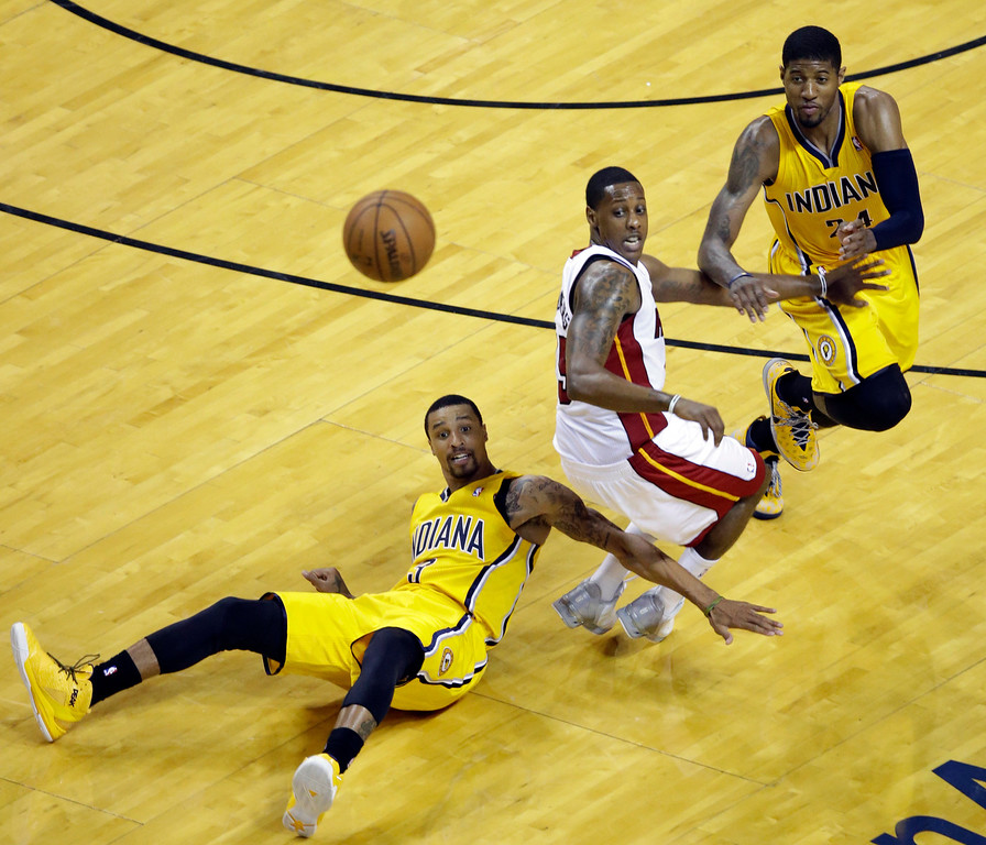 . Indiana Pacers forward Paul George, right, and Miami Heat guard Mario Chalmers, center, look back as Pacers guard George Hill (3) loses the ball during the second half of Game 6 in the NBA basketball playoffs Eastern Conference finals on Friday, May 30, 2014, in Miami. (AP Photo/Wilfredo Lee)