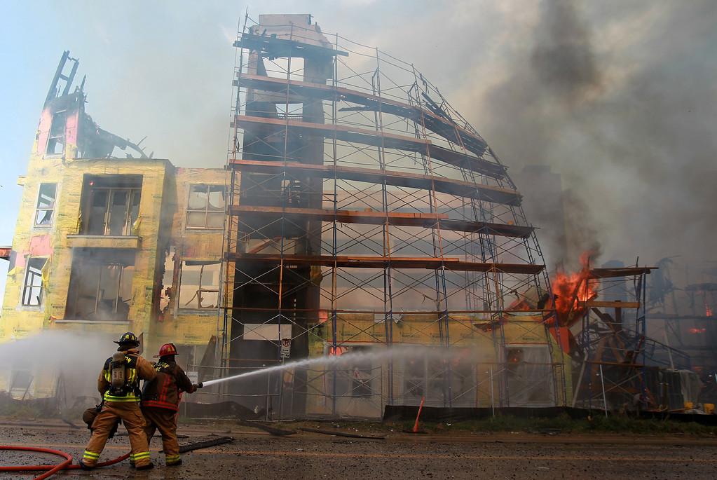 . Houston firefighters spray water trying to extinguish a five-alarm fire at a construction site Tuesday, March 25, 2014, in Houston.  (AP Photo/Houston Chronicle, Mayra Beltran)