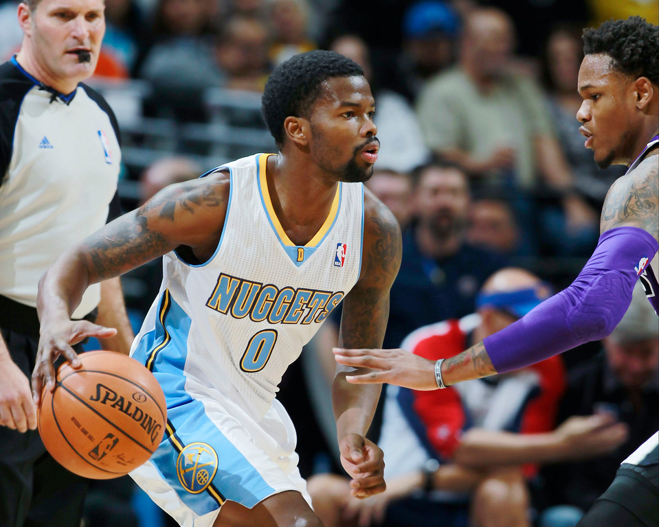 . Denver Nuggets guard Aaron Brooks, left,  dibbles the ball as Sacramento Kings guard Ben McLemore covers in the first quarter of an NBA basketball game in Denver, Sunday, Feb. 23, 2014. (AP Photo/David Zalubowski)