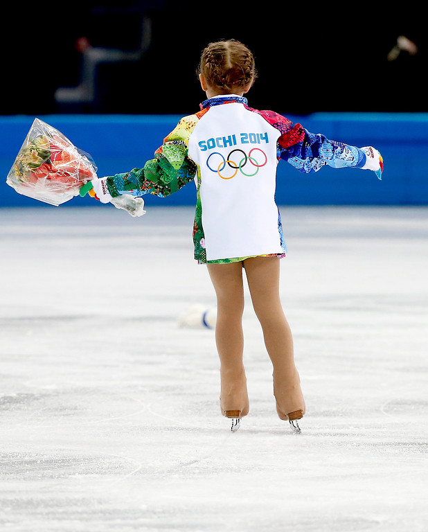 Description of . A flower girl collects flowers during the Pairs Short Program of the Figure Skating event at Iceberg Palace during the Sochi 2014 Olympic Games, Sochi, Russia, 11 February 2014.  EPA/HOW HWEE YOUNG