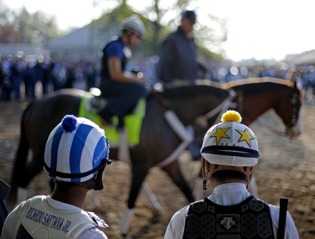 . Some jockeys watch as Kentucky Derby hopeful Oxbow walks to the track for a workout at Churchill Downs Wednesday, May 1, 2013, in Louisville, Ky. (AP Photo/David Goldman)