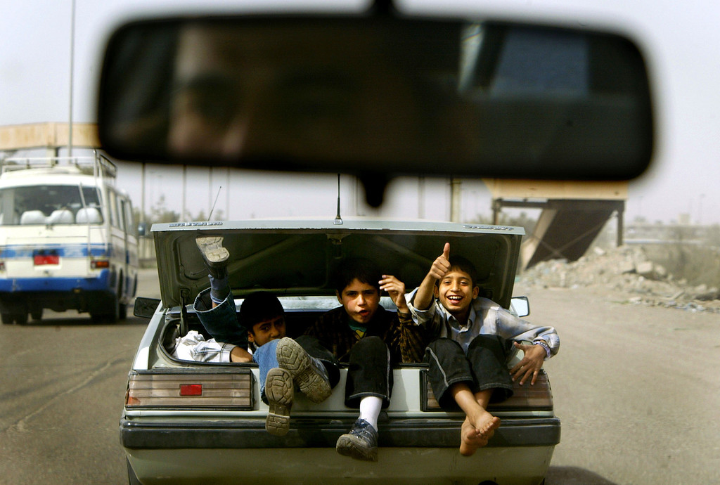 . Boys wave as they ride in the trunk of a car February 19, 2004 in Baghdad, Iraq. (Photo by Mario Tama/Getty Images)