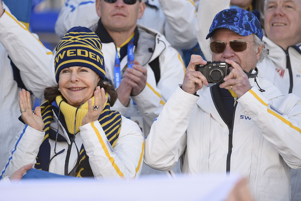 . Swedish royals, King Carl XVI Gustaf and Queen Silvia, watch as Sweden\'s Gold Medallist relay team goes to the podium during the Women\'s Cross-Country Skiing 4x5km Relay Flower Ceremony at the Laura Cross-Country Ski and Biathlon Center during the Sochi Winter Olympics on February 15, 2014, in Rosa Khutor near Sochi. ODD ANDERSEN/AFP/Getty Images