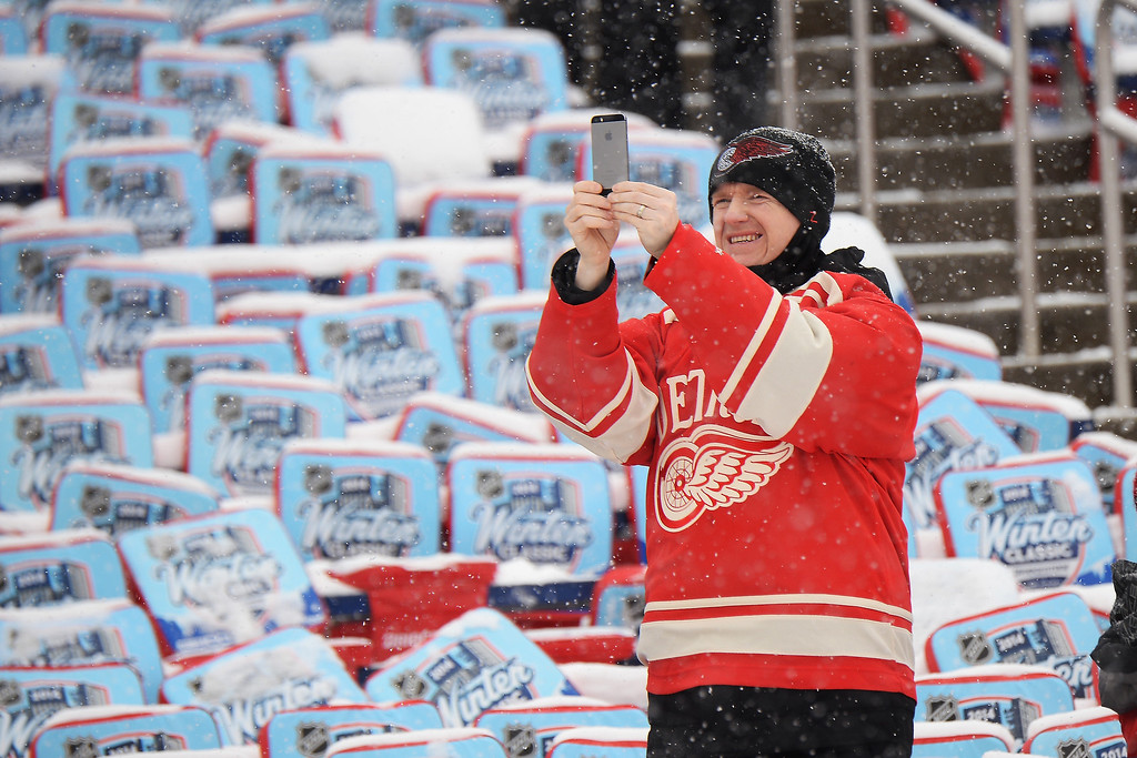 . A Detroit Red Wings fan captures the moment prior to the 2014 Bridgestone NHL Winter Classic on January 1, 2014 at Michigan Stadium in Ann Arbor, Michigan.  (Photo by Jamie Sabau/Getty Images)