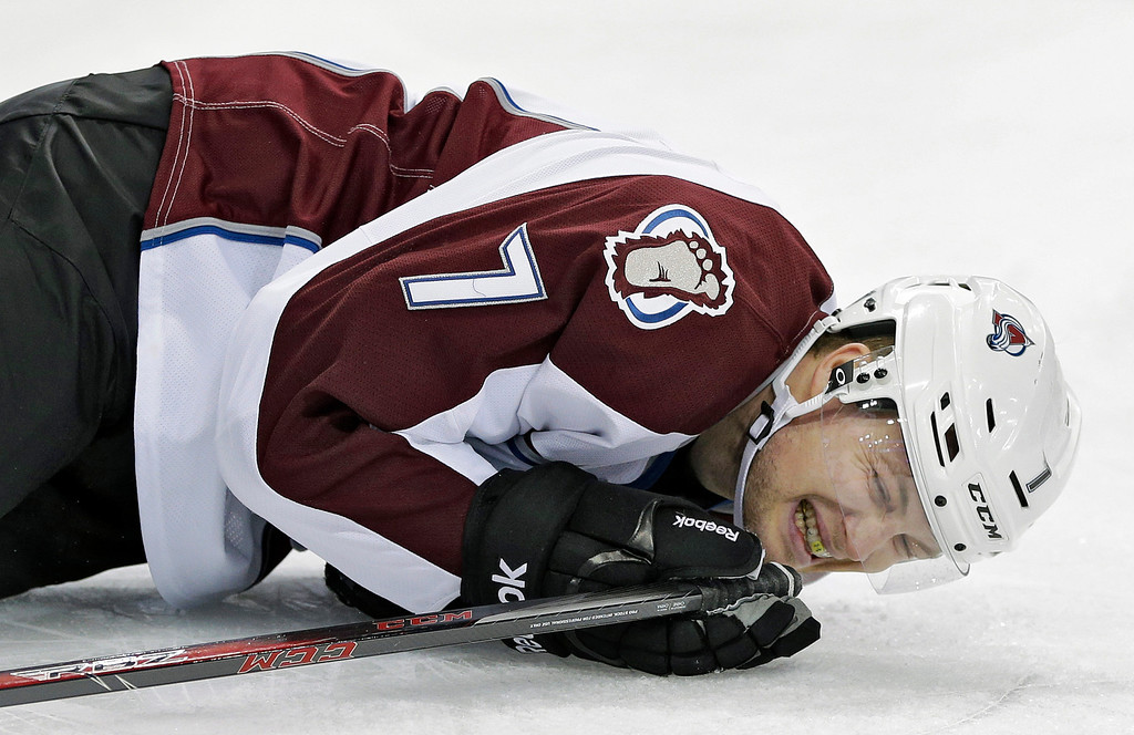 . Colorado Avalanche center John Mitchell grimaces in pain after being boarded by Tampa Bay Lightning right wing B.J. Crombeen during the first period of an NHL hockey game Saturday, Jan. 25, 2014, in Tampa, Fla. Crombeen was penalized on the play. (AP Photo/Chris O\'Meara)