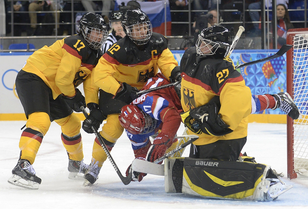 . Russia\'s Yekaterina Smolentseva (2nd R) is sandwiched between Germany\'s goalkeeper Viona Harrer (R), Susann Goetz (2nd R) and Sara Seiler (L) during a Women\'s Ice Hockey Group B match between Russia and Germany at the Shayba Arena during the Sochi Winter Olympics on February 9, 2014.   ALEXANDER NEMENOV/AFP/Getty Images