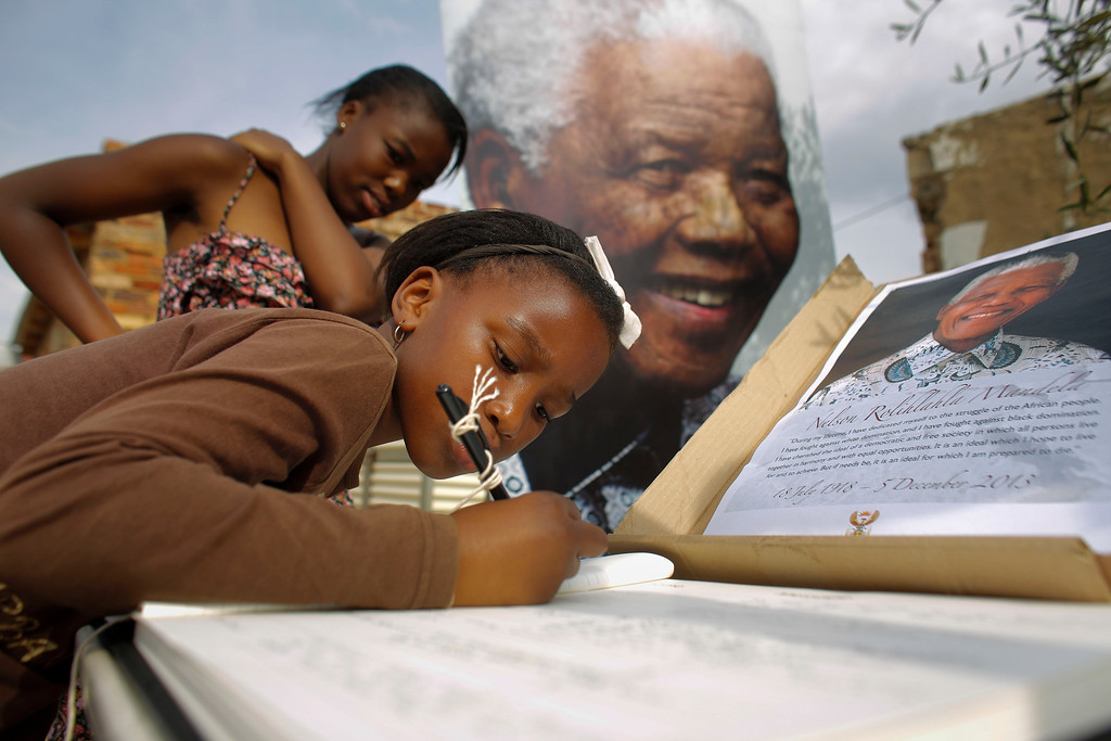 . The sisters Ayanda, background, and Ntombi Ntshingita  sign a condolence book for former president Nelson Mandela outside his first township home in Alexandra in Johannesburg, Saturday, Dec. 7, 2013. Mandela moves to the house at Alexandra in 1941.  (AP Photo/Markus Schreiber)