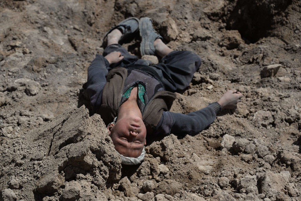 . An orphaned young Afghan villager, who lost his family in the landslide, lies in the dirt as he grieves at the scene in Aab Bareek village in Argo district of Badakhshan on May 5, 2014.  AFP PHOTO/FARSHAD  USYAN/AFP/Getty Images