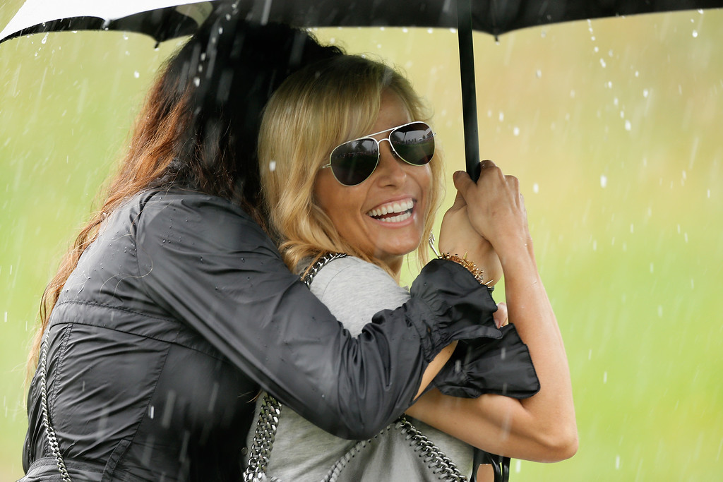 . DUBLIN, OH - OCTOBER 05:  Amy Mickelson waits under an umbrella during a weather-delay during the Day Three Four-ball Matches at the Muirfield Village Golf Club on October 5, 2013  in Dublin, Ohio.  (Photo by Gregory Shamus/Getty Images)