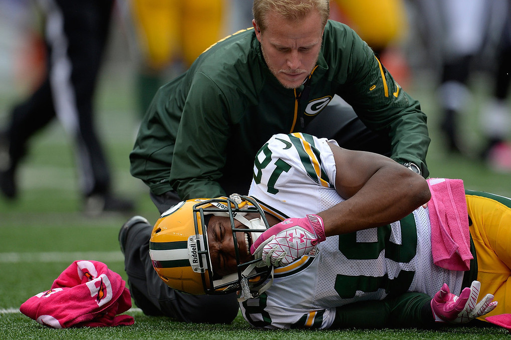 . Randall Cobb #18 of the Green Bay Packers is attended to by a trainer after being injuired on a play in the second quarter during a game against the Baltimore Ravens at M&T Bank Stadium on October 13, 2013 in Baltimore, Maryland.  (Photo by Patrick McDermott/Getty Images)