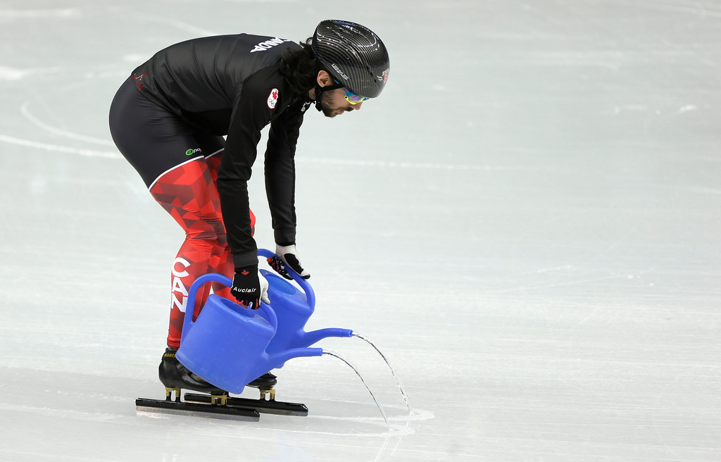 . Canadian short track speed skating team member Charles Hamelin pours water on the ice during a training session at the Iceberg Skating Palace ahead of the 2014 Winter Olympics, Tuesday, Feb. 4, 2014, in Sochi, Russia. (AP Photo/Mark Baker)