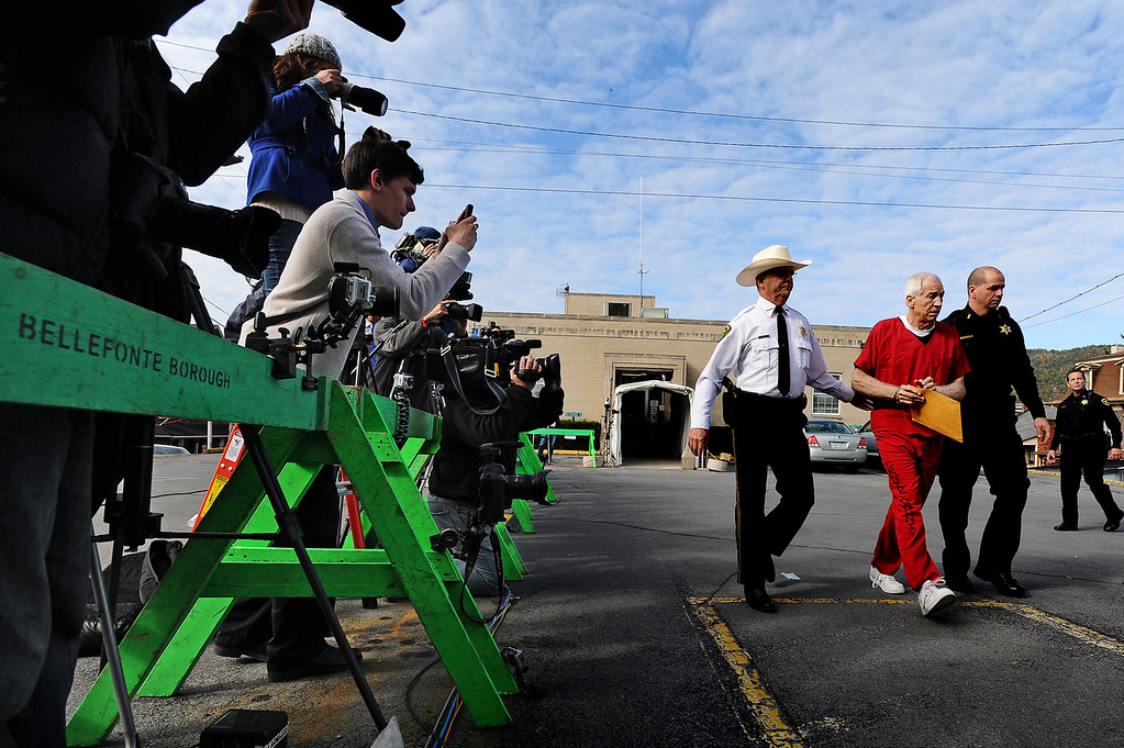 . Former Penn State assistant football coach Jerry Sandusky (2nd R) leaves the Centre County Courthouse after being sentenced in his child sex abuse case on October 9, 2012 in Bellefonte, Pennsylvania. The 68-year-old Sandusky was sentenced to at least 30 years and not more that 60 years in prison for his conviction in June on 45 counts of child sexual abuse, including while he was the defensive coordinator for the Penn State college football team. (Photo by Patrick Smith/Getty Images)