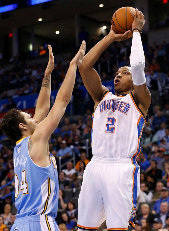 . Oklahoma City Thunder forward Caron Butler shoots over Denver Nuggets guard Evan Fournier (94) in the fourth quarter of an NBA basketball game in Oklahoma City, Monday, March 24, 2014. Oklahoma City won 117-96. (AP Photo/Sue Ogrocki)