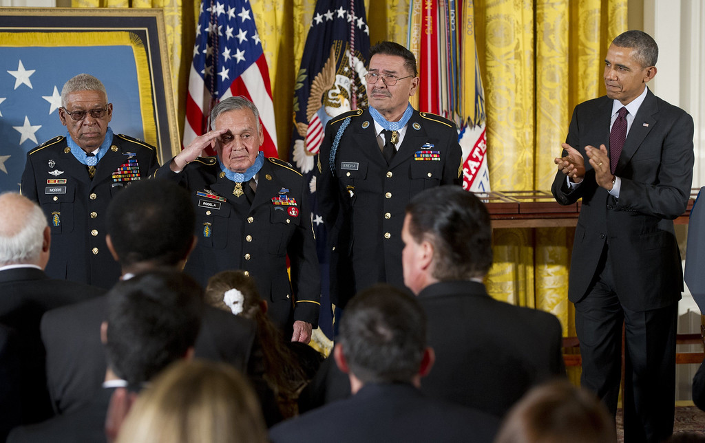 . US President Barack Obama applauds Medal of Honor recipients Staff Sergeant Melvin Morris (L), Sergeant First Class Jose Rodela (2nd L) and Specialist Four Santiago Erevia (3rd R) for actions during the Vietnam War, during a ceremony in the East Room of the White House in Washington on March 18, 2014.   AFP PHOTO / Saul LOEB/AFP/Getty Images