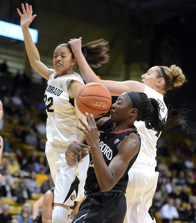 . Arielle Roberson, left, and Jen Reese of CU, battle with Chiney Ogwumike of Stanford during the first half of the January 12, 2014 game in Boulder. Cliff Grassmick/Daily Camera