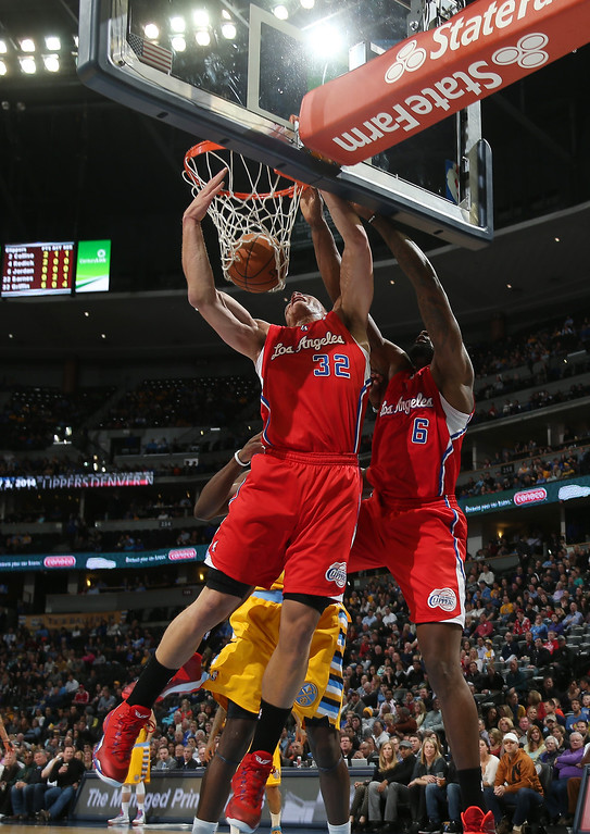 . Los Angeles Clippers forward Blake Griffin, left, dunks ball in front of DeAndre Jordan, right, as Denver Nuggets forward J.J. Hickson covers in the first quarter of an NBA basketball game in Denver, Monday, Feb. 3, 2014. (AP Photo/David Zalubowski)