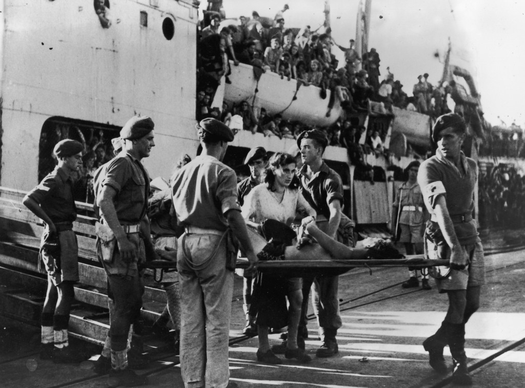 . October 1947:  Medical orderlies carrying a sick illegal immigrant off the ship \'Jewish State\' at the harbour in Haifa. The man\'s wife accompanies the troops. The ship was then sent on to Cyprus.  (Photo by Keystone/Getty Images)