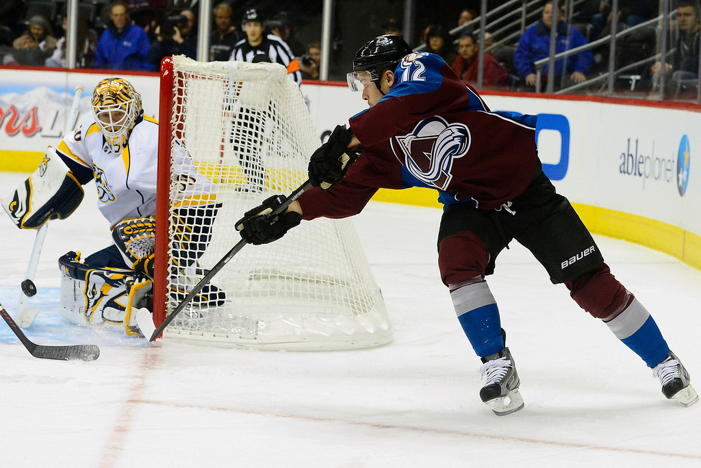 . Chris Mason (30) of the Nashville Predators eyes a shot by Chuck Kobasew (12) of the Colorado Avalanche during the first period of action. The Colorado Avalanche take on the Nashville Predators at the Pepsi Center on February 18, 2013. (Photo By AAron Ontiveroz/The Denver Post)