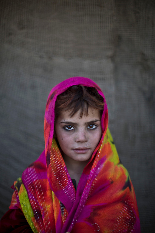 . In this Saturday, Jan. 25, 2014 photo, Afghan refugee girl, Nazmina Bibi, 7, poses for a picture, while playing with other children in a slum on the outskirts of Islamabad, Pakistan. For more than three decades, Pakistan has been home to one of the world�s largest refugee communities: hundreds of thousands of Afghans who have fled the repeated wars and fighting their country has undergone. Since the 2002 U.S.-led invasion of Afghanistan, some 3.8 million Afghans have returned to their home country, according to the U.N.�s refugee agency. (AP Photo/Muhammed Muheisen)