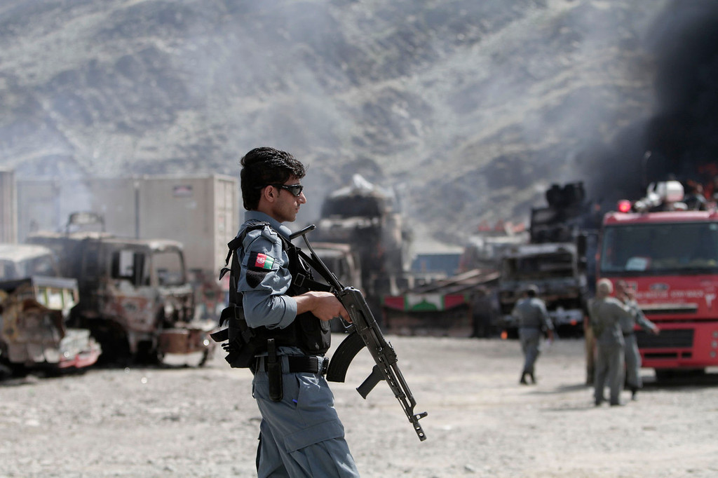 . An Afghan policeman stands guard near burning NATO supply trucks following an attack by militants in the Torkham area near the Pakistan-Afghanistan border in Jalalabad province east of Kabul, Afghanistan, Monday, Sept. 2, 2013. The Taliban claimed responsibility for the strike on a U.S. base in Afghanistan near the border with Pakistan on Monday, setting off bombs, torching vehicles and shutting down a key road used by NATO supply trucks, officials said. Several people were killed.   (AP Photo/Rahmat Gul)