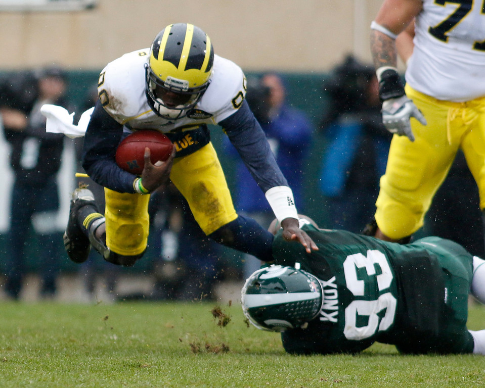 . Michigan quarterback Devin Gardner, left, is tripped up by Michigan State\'s Damon Knox (93) during the first quarter of an NCAA college football game, Saturday, Nov. 2, 2013, in East Lansing, Mich. Michigan State won 29-6. (AP Photo/Al Goldis)