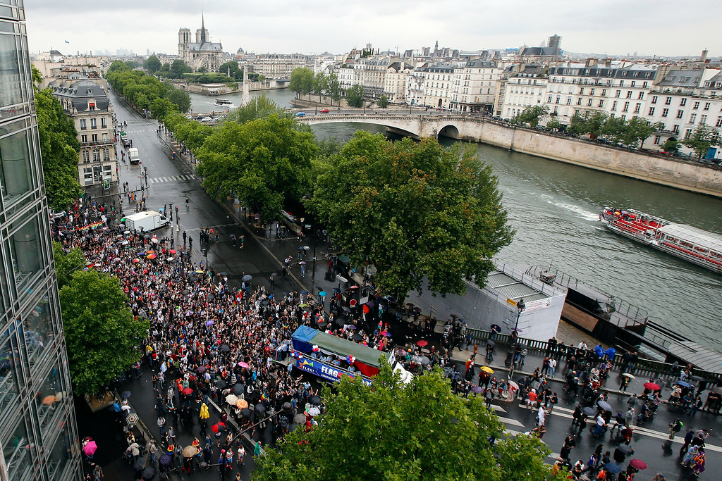 . Revelers parade on the Sully bridge on The Seine River with Notre Dame Cathedral in background during the annual Gay Pride march in Paris, France, Saturday, June 28, 2014.Around the globe, LGBT Pride Month has been marked with parades and marches, festivals and dances, and in some cases, protests and counter-protests.  (AP Photo/Francois Mori)