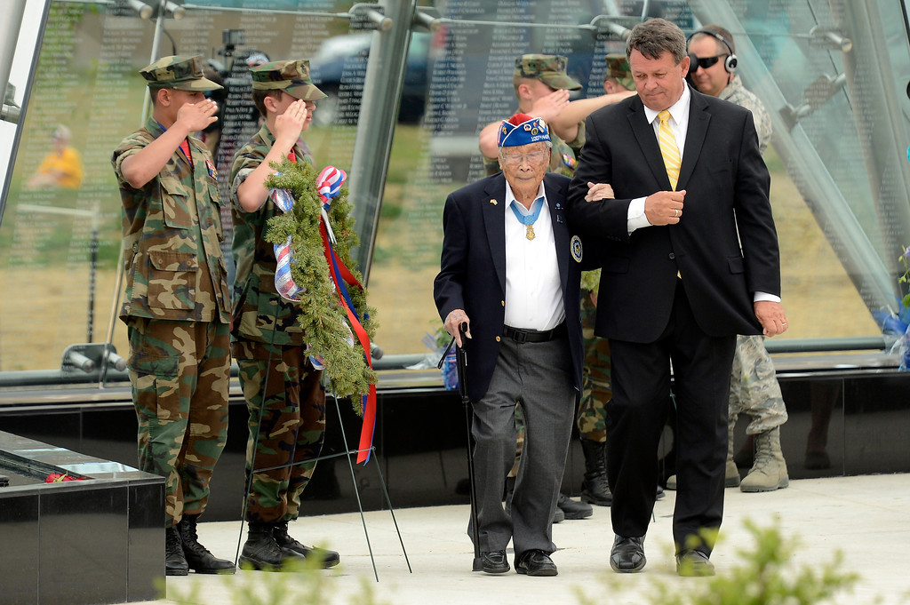 . Rick Carandall escorts George Sakato 92-years-old ack to his seat during the Colorado Freedom Memorial dedication May 26, 2013 in Aurora. Private George T. Sakato distinguished himself by extraordinary heroism in action on 29 October 1944, on hill 617 in the vicinity of Biffontaine, France. After his platoon had virtually destroyed two enemy defense lines, during which he personally killed five enemy soldiers and captured four, his unit was pinned down by heavy enemy fire. The memorial was funded through a radio blitz drive last year by KEZW, is officially dedicated. The memorial is a 21 glass panel and bears the names of nearly 6,000 Coloradans killed or MIA in all wars. (Photo By John Leyba/The Denver Post)