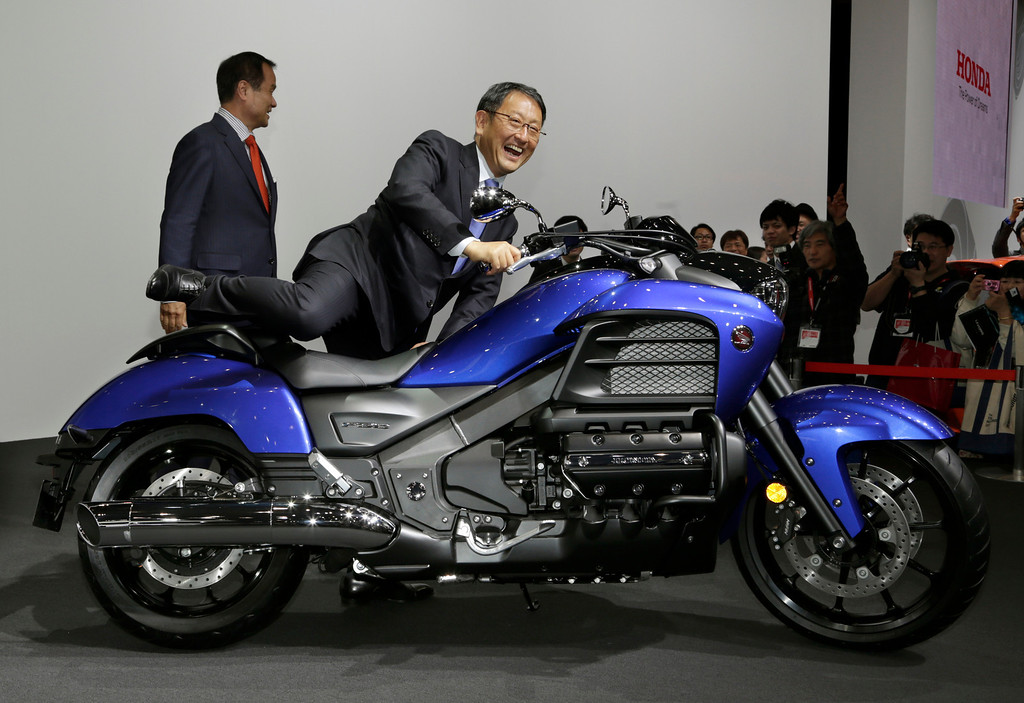 . Toyota Motor Corp. President Akio Toyoda, rides on Honda Gold Wing F6C as Honda Motor Co. President Takanobu Ito stands by at the media preview for the Tokyo Motor Show at Tokyo Big Sight convention hall in Tokyo Wednesday, Nov. 20, 2013. The biannual exhibition of vehicles in Japan runs for the public from Saturday, Nov. 23 through Dec. 1. (AP Photo/Shizuo Kambayashi)