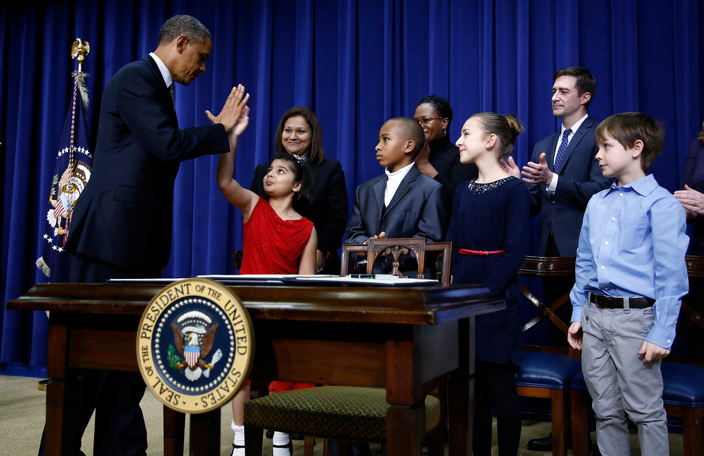 . U.S. President Barack Obama high-fives eight-year-old Hinna Zejah after unveiling a series of gun control proposals during an event at the White House in Washington, January 16, 2013. Hinna and her mother Nadia (Behind L) was among a group of children and families of children who wrote the president letters about guns and gun control after the December 14 school shooting in Newtown, Connecticut, in which 20 children and six adults were killed. REUTERS/Jason Reed