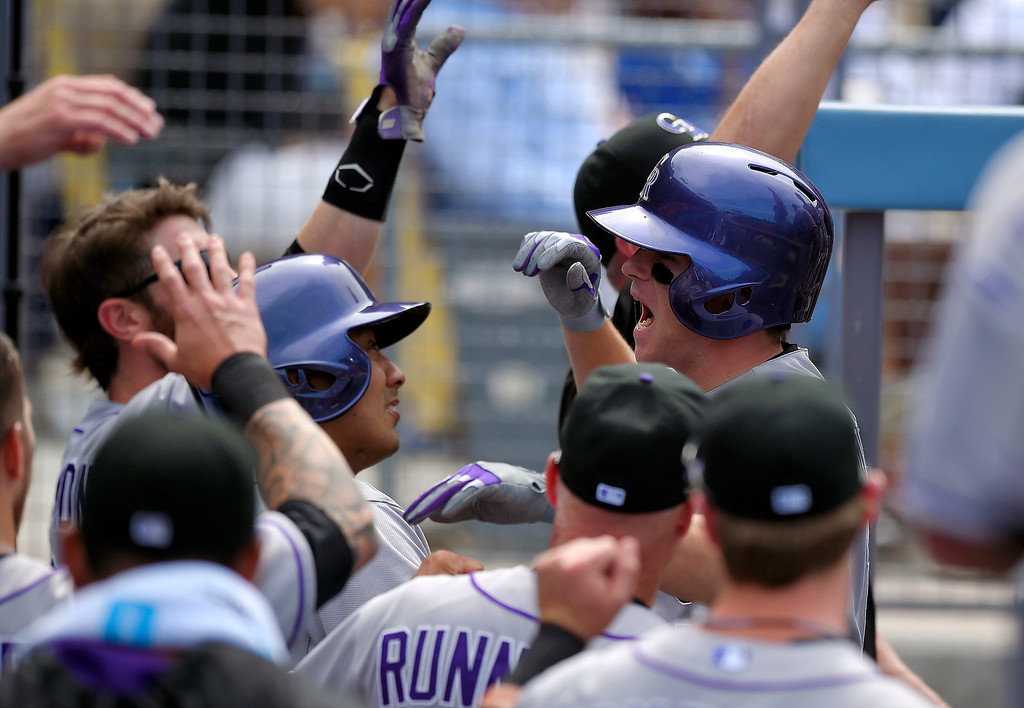. Colorado Rockies\' Josh Rutledge, right, is congratulated after hitting a three-run home run during the sixth inning of a baseball game Los Angeles Dodgers, Sunday, April 27, 2014, in Los Angeles. (AP Photo/Mark J. Terrill)