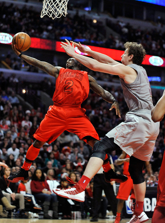 . Chicago Bulls\' Nate Robinson (2) shoots against Houston Rockets\' Omer Asik in the fourth quarter of an NBA basketball game in Chicago, Tuesday, Dec. 25, 2012. Houston won 120-97. (AP Photo/Paul Beaty)