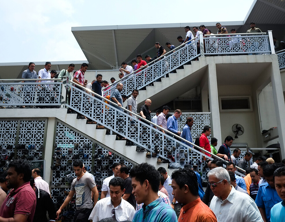 . Muslims exit a mosque after performing their Friday prayers for the missing passengers at a mosque on March 21, 2014 in Kuala Lumpur, Malaysia. Australian authorities yesterday received satellite imagery that shows two large objects in the Indian Ocean that may be debris from missing Malaysian Airlines flight MH370.  The airliner went missing nearly two weeks ago carrying 239 passengers and crew on route from Kuala Lumpur to Beijing.  (Photo by Rahman Roslan/Getty Images)