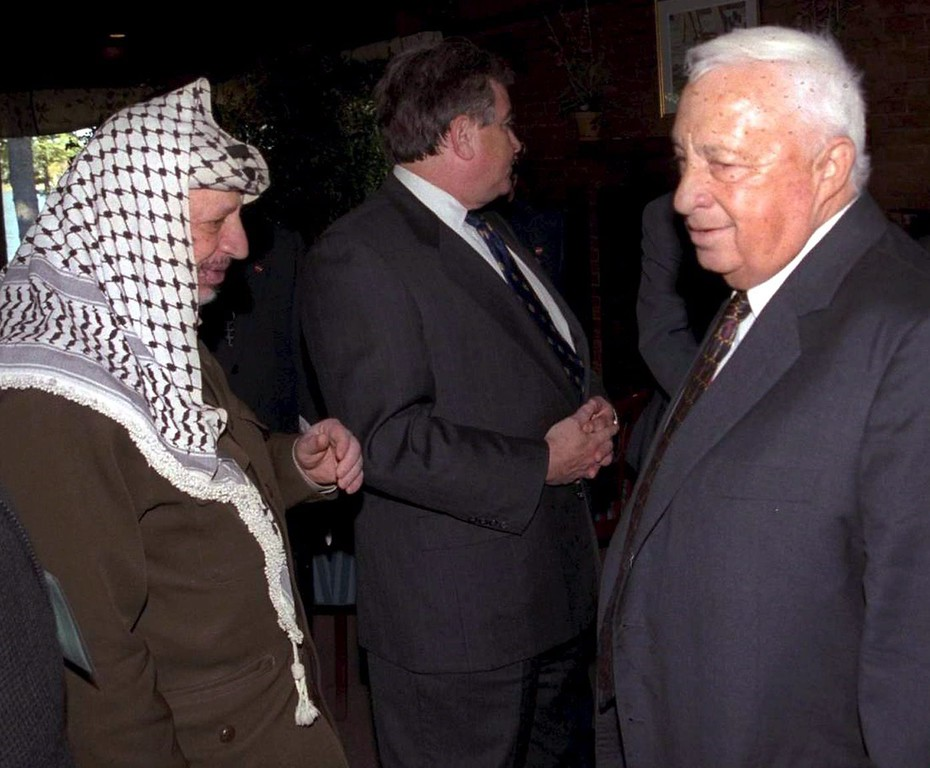 . A handout picture dated 21 October 1998 supplied by the Israeli Government Press Office shows then Foreign Minister Ariel Sharon (R) as he approaches Palestinian President Yasser Arafat (L) during Israeli-Palestinian negotiations hosted by US President Bill Clinton at the Wye Plantation near Washington DC, USA. EPA/AVI OHAYON/GPO