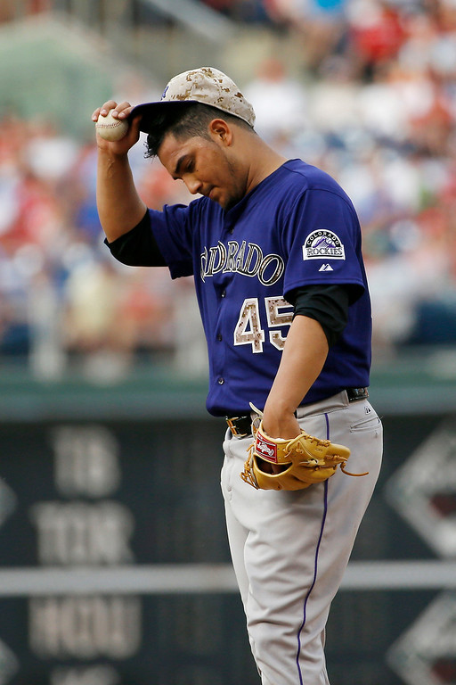 . Colorado Rockies starting pitcher Jhoulys Chacin adjusts his hat after giving up an RBI-single to Philadelphia Phillies\' Ben Revere during the fifth inning of a baseball game, Monday, May 26, 2014, in Philadelphia. Philadelphia won 9-0. (AP Photo/Matt Slocum)