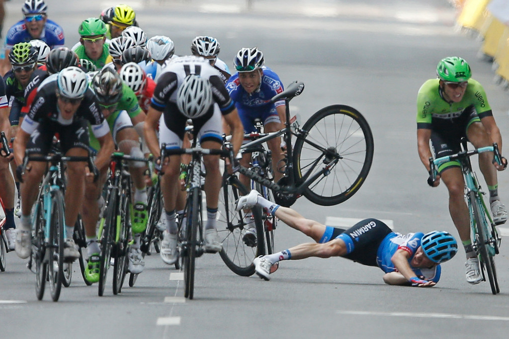 . Andrew Talansky of the U.S. crashes as the pack with stage winner Italy\'s Matteo Trentin, foreground left, sprints towards the finish line during the seventh stage of the Tour de France cycling race over 234.5 kilometers (145.7 miles) with start in Epernay and finish in Nancy, France, Friday, July 11, 2014. (AP Photo/Peter Dejong)