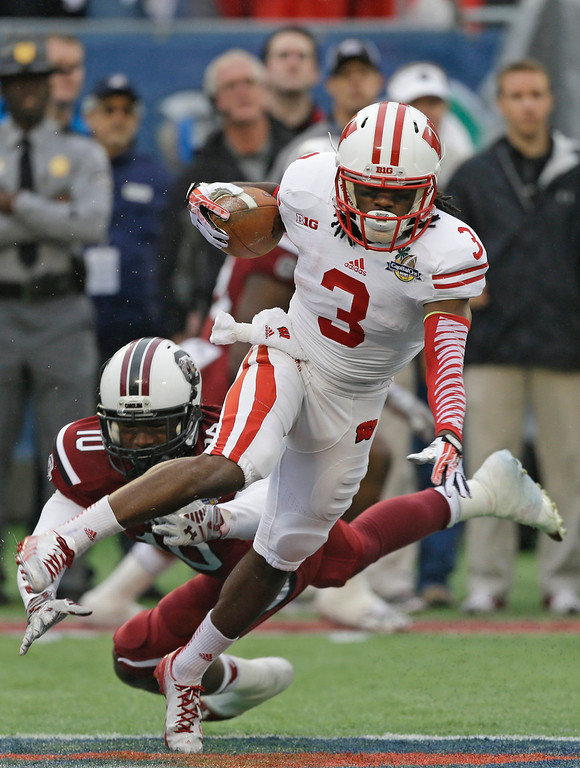 . Wisconsin\'s Kenzel Doe (3) runs past South Carolina\'s Skai Moore (10)  on a kickoff return during the first half of the Capital One Bowl NCAA college football game in Orlando, Fla., Wednesday, Jan. 1, 2014.(AP Photo/John Raoux)