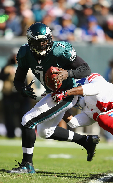 . Michael Vick #7 of the Philadelphia Eagles scrambles out of the grasp of  Mathias Kiwanuka #94 of the New York Giants  during their game at Lincoln Financial Field on October 27, 2013 in Philadelphia, Pennsylvania.  (Photo by Al Bello/Getty Images)