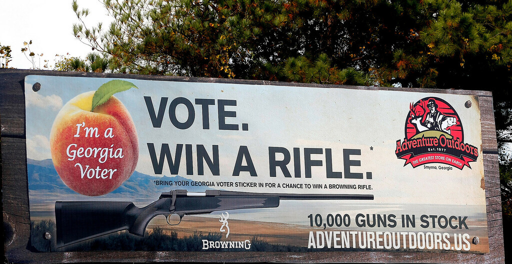 """. One of several billboards of a gun raffle promotion at Adventures Outdoors in Smyrna, Georgia, October 25, 2012. The store has promoted the raffle on billboards as a \""""Vote. Win a rifle.\"""" but owner Jay Wallace has stated that all Georgia residents were eligible to enter.  REUTERS/Tami Chappell"""