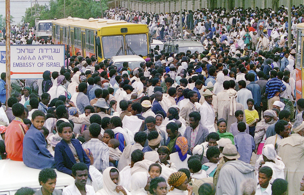 ". ADDIS ABEBA, ETHIOPIA:  Ethiopian Jews, known as ""Falasha\"", gather in the thousands outside the Israeli embassy, 24 May 1991, in Addis Ababa, waiting to be bussed to the airport. Israel is planning to take about 1,000 refuges a week out of the country as the civil war continues. JEROME DELAY/AFP/Getty Images"