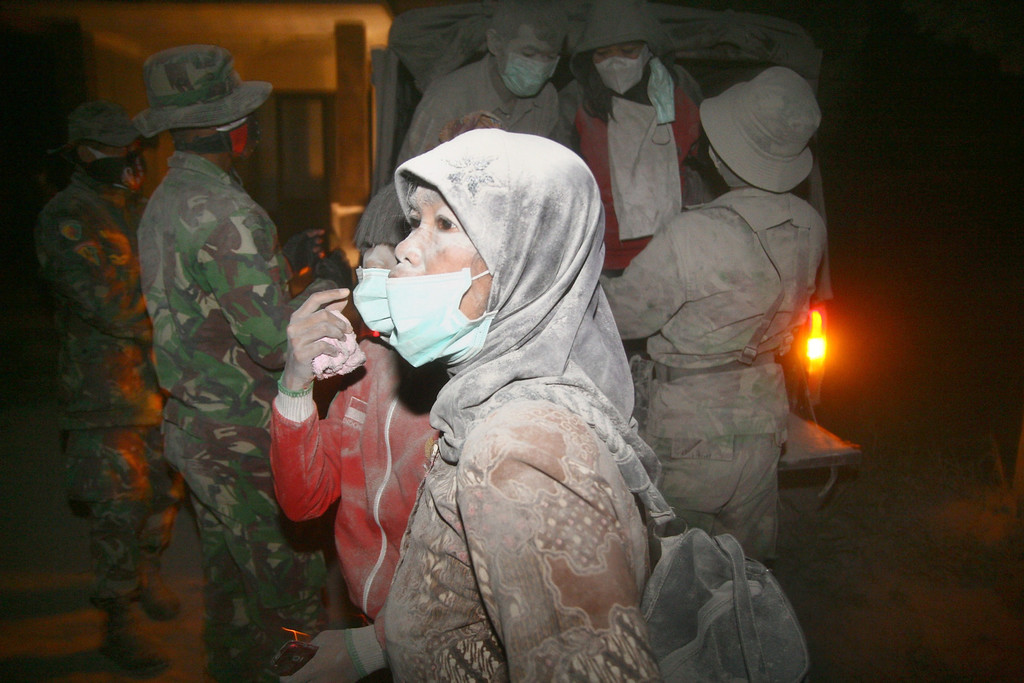 . Indonesian soldiers evacuate ash covered residents in Malang, East Java province on February 14, 2014 following the eruption of Mount Kelud volcano. AFP PHOTO / AMAN ROCHMAN/AFP/Getty Images