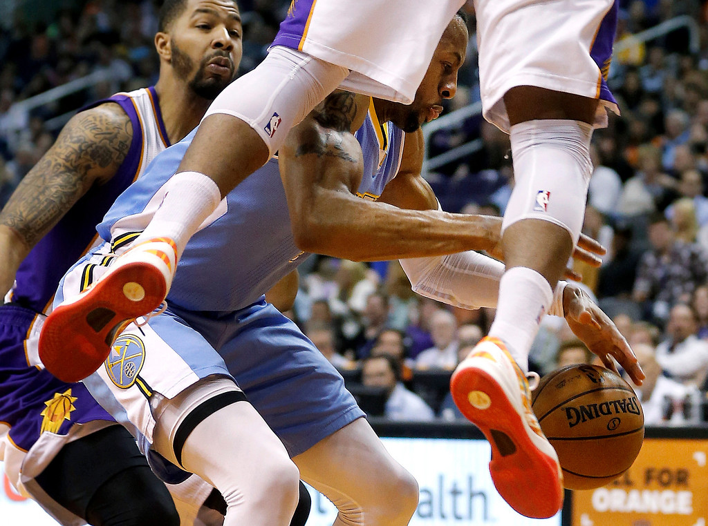 . Denver Nuggets\' Andre Iguodala chases a loose ball as Phoenix Suns\' Markieff Morris, left, and P.J. Tucker defend during the first half of an NBA basketball game, Monday, March 11, 2013, in Phoenix. (AP Photo/Matt York)