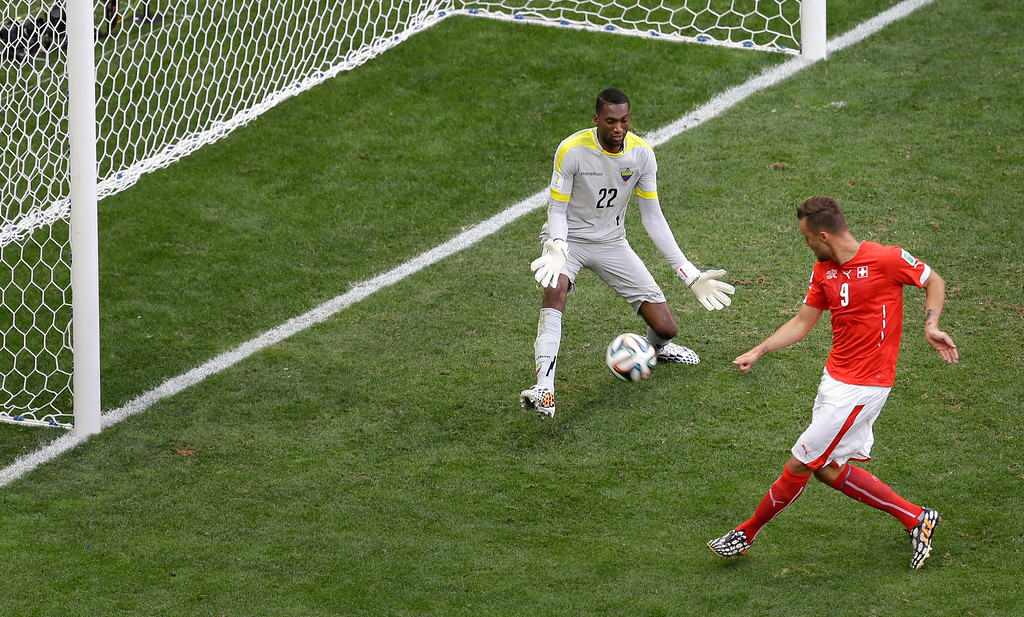 . Switzerland\'s Haris Seferovic, right, scores his side\'s second goal past Ecuador\'s goalkeeper Alexander Dominguez during the group E World Cup soccer match between Switzerland and Ecuador at the Estadio Nacional in Brasilia, Brazil, Sunday, June 15, 2014. Switzerland defeated Ecuador 2-1. (AP Photo/Themba Hadebe)